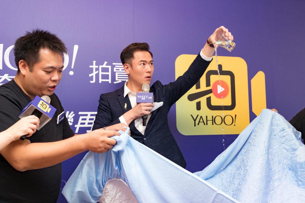 「ALICE愛利斯寢飾」店家郭豐旭(左),直播時將水倒到床包上展示防水效果